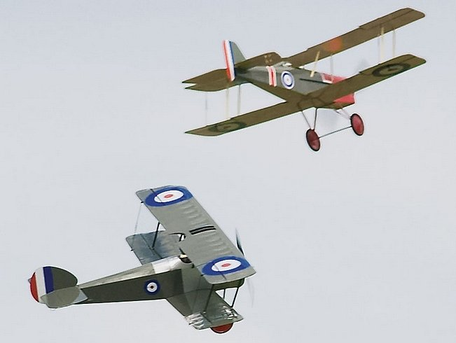 In flight shot of 2 scale park flyers, flying close.